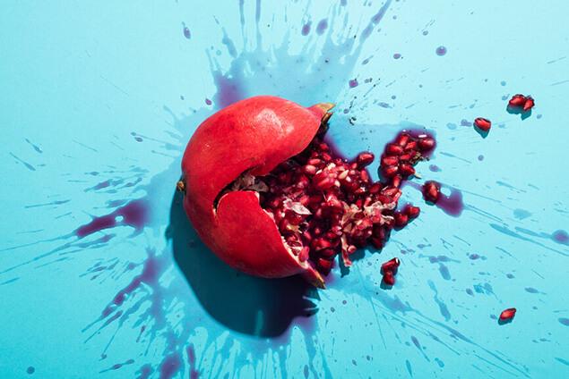 Aufgeplatzter Granatapfel in rot vor blauem Hintergrund