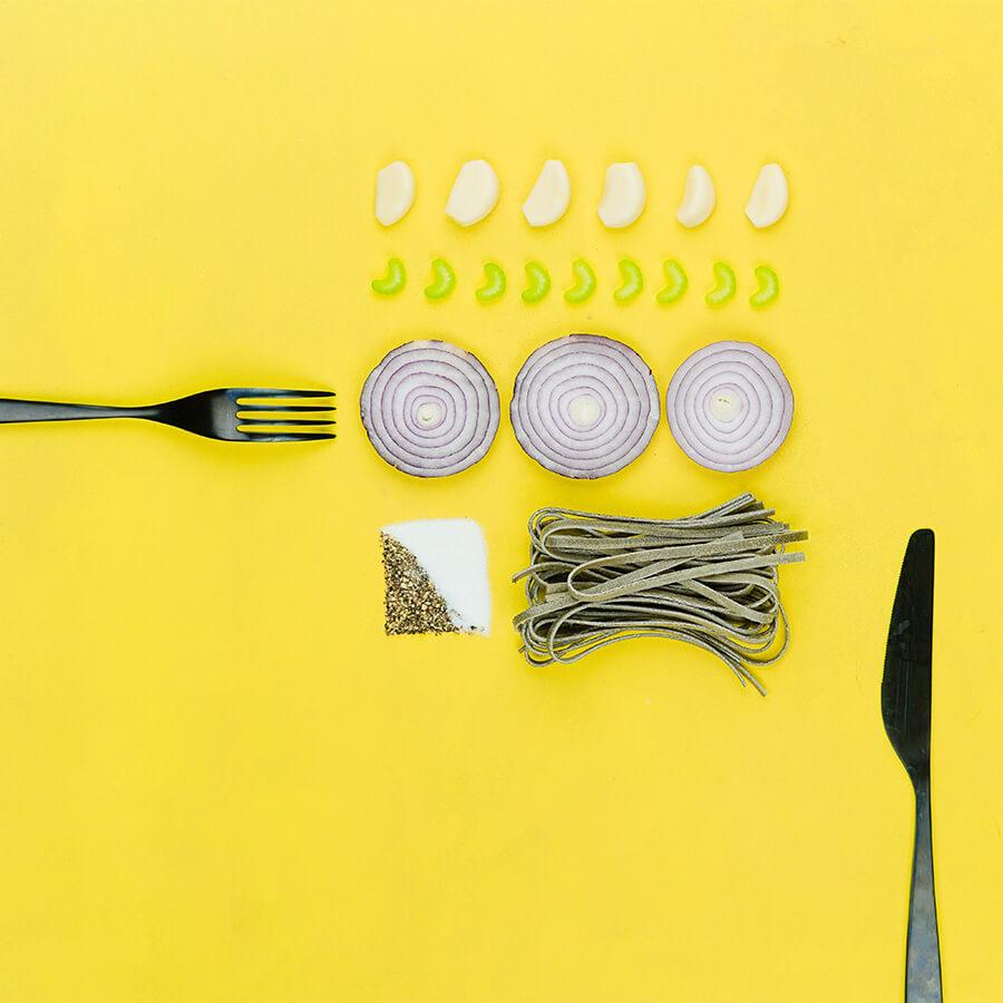 Messer, Gabel, Pasta, Zwiebel und Knoblauch vor gelbem Hintergrund